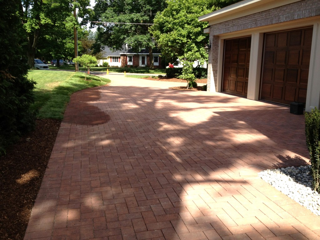 two door garage with brick driveway