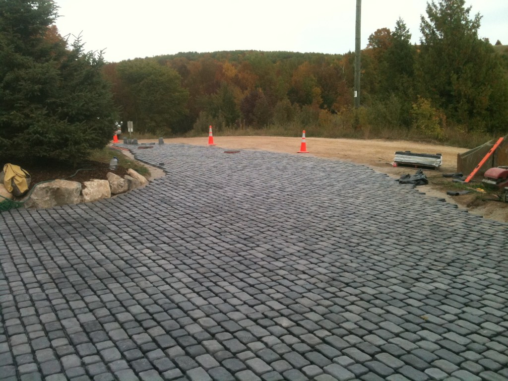 gray rounded paver stones that meet a dirt road