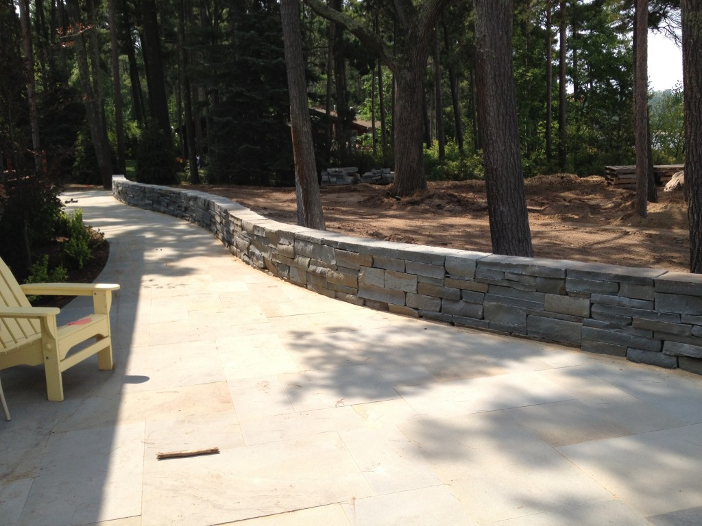 short stone wall along smooth paved walkway
