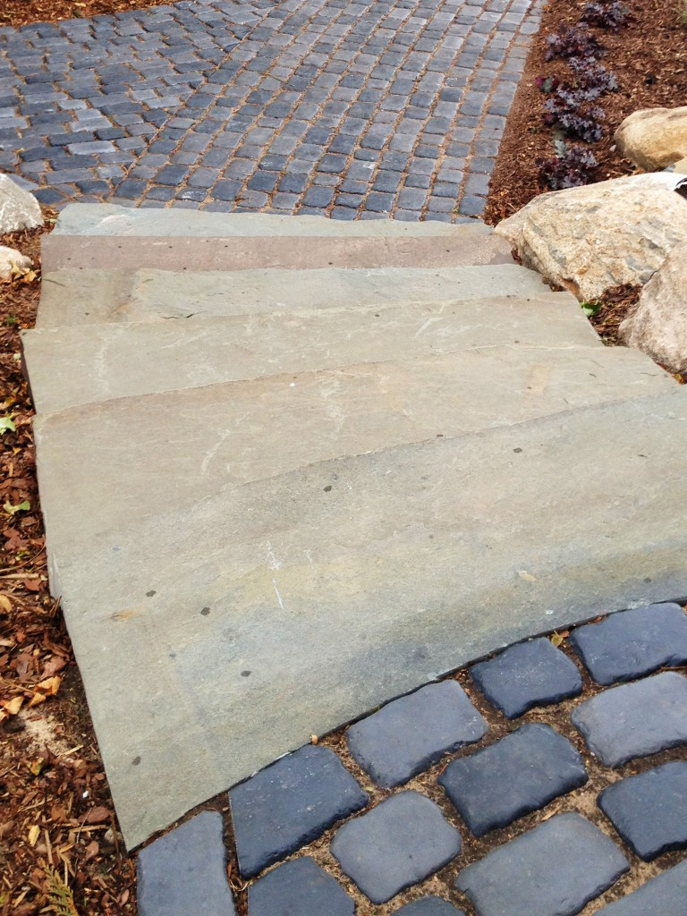 multi colored stone slab stairway between dark gray pavers