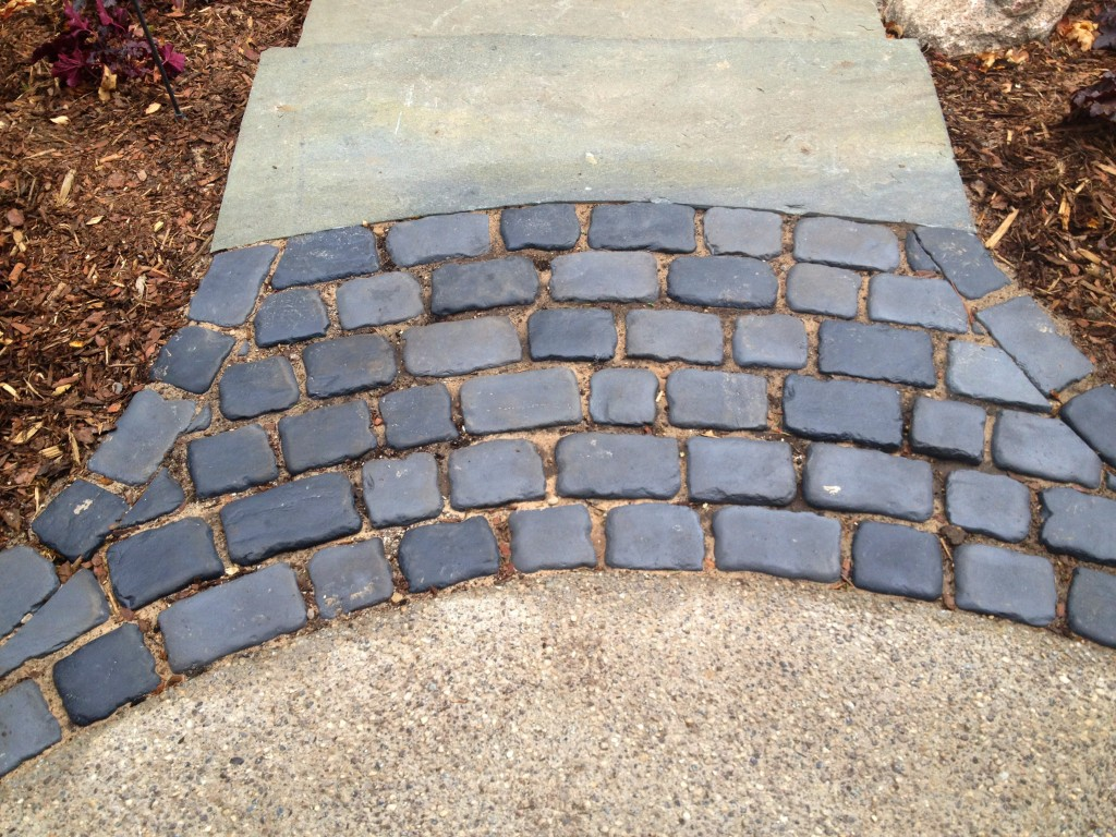 dark gray paver pathway between driveway and patio