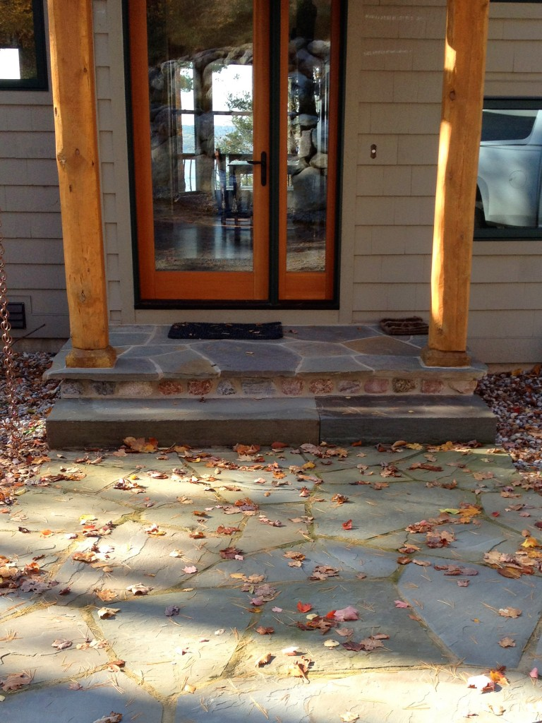 flat stone porch with natural wood beam pillars