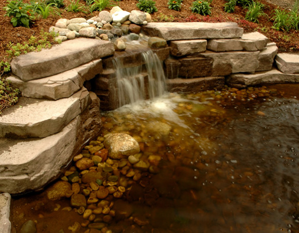 tiered rock waterfall draining into pond