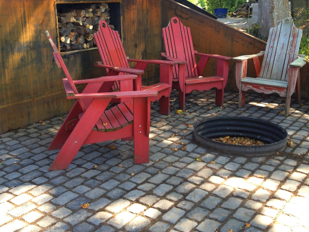 three red adirondack chairs around a fire pit