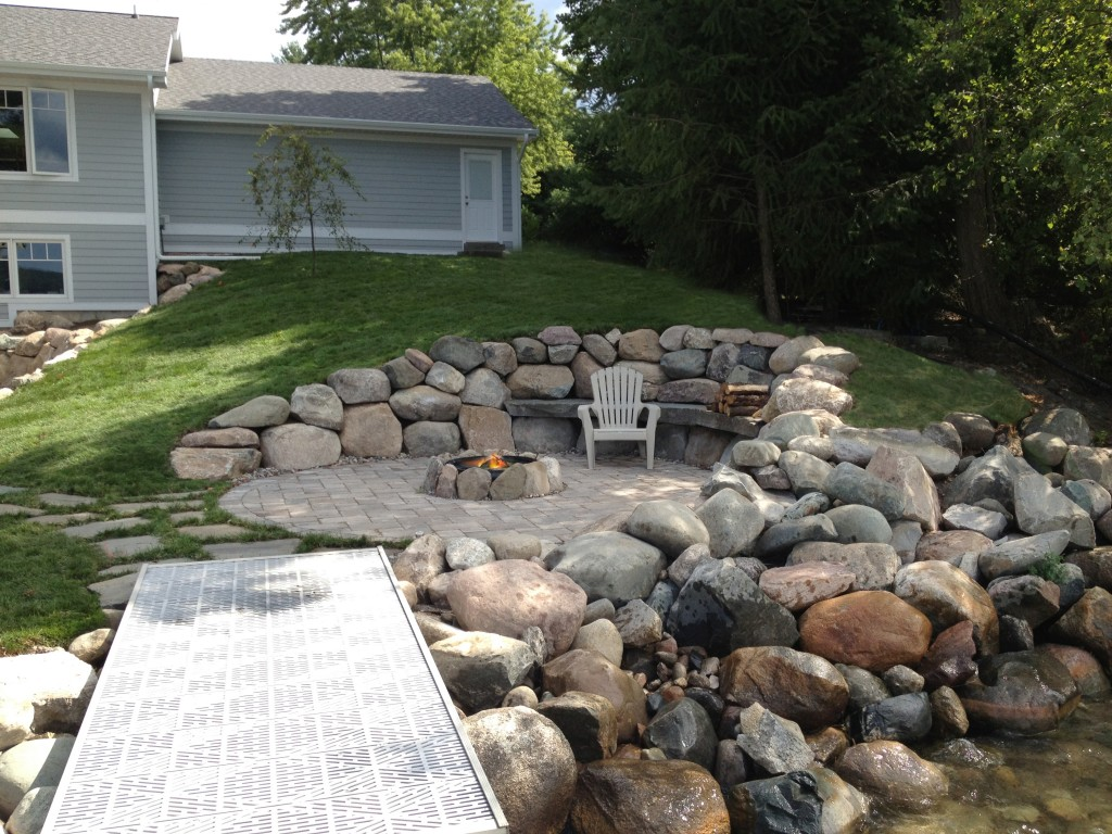 large rock retaining wall landscape feature with fire pit