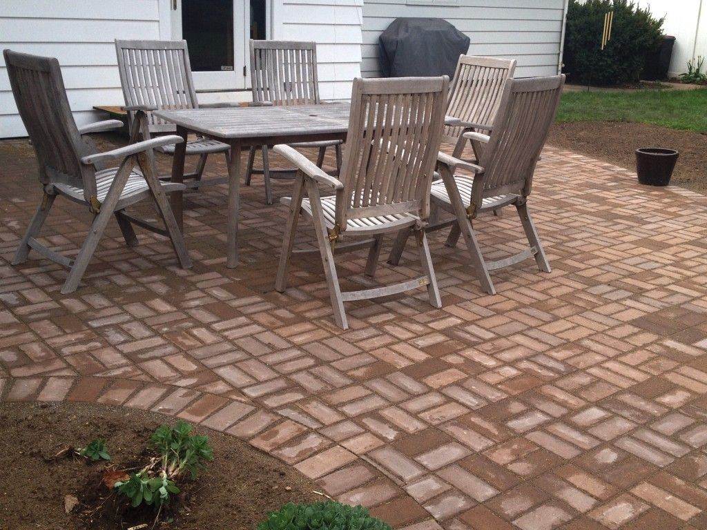 wet brick patio with wooden table and chairs