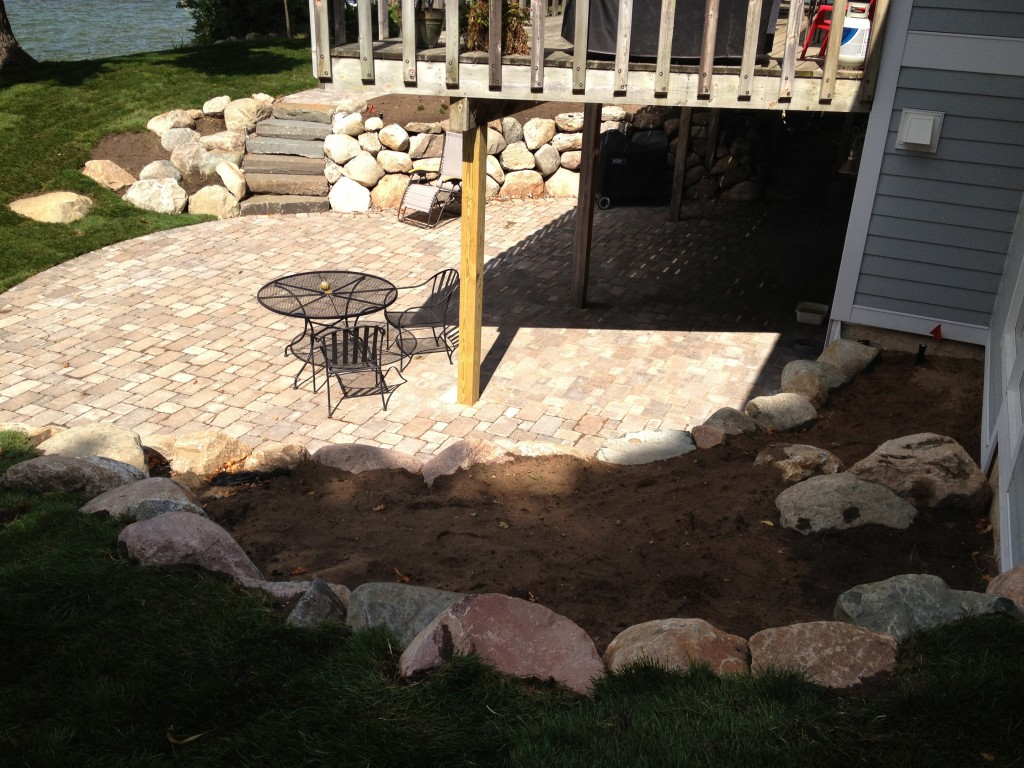 backyard landscaped using a mixture of large stones and pavers