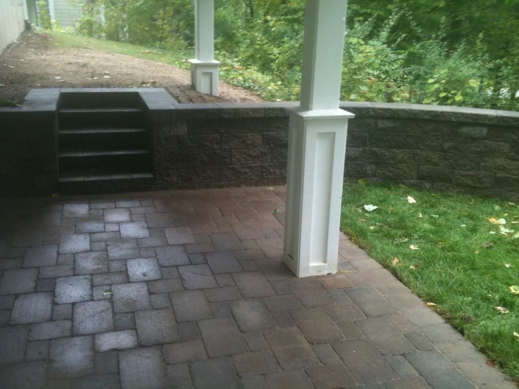 paved basement walkout with wooded surroundings