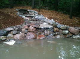 custom made water fall into man made pond