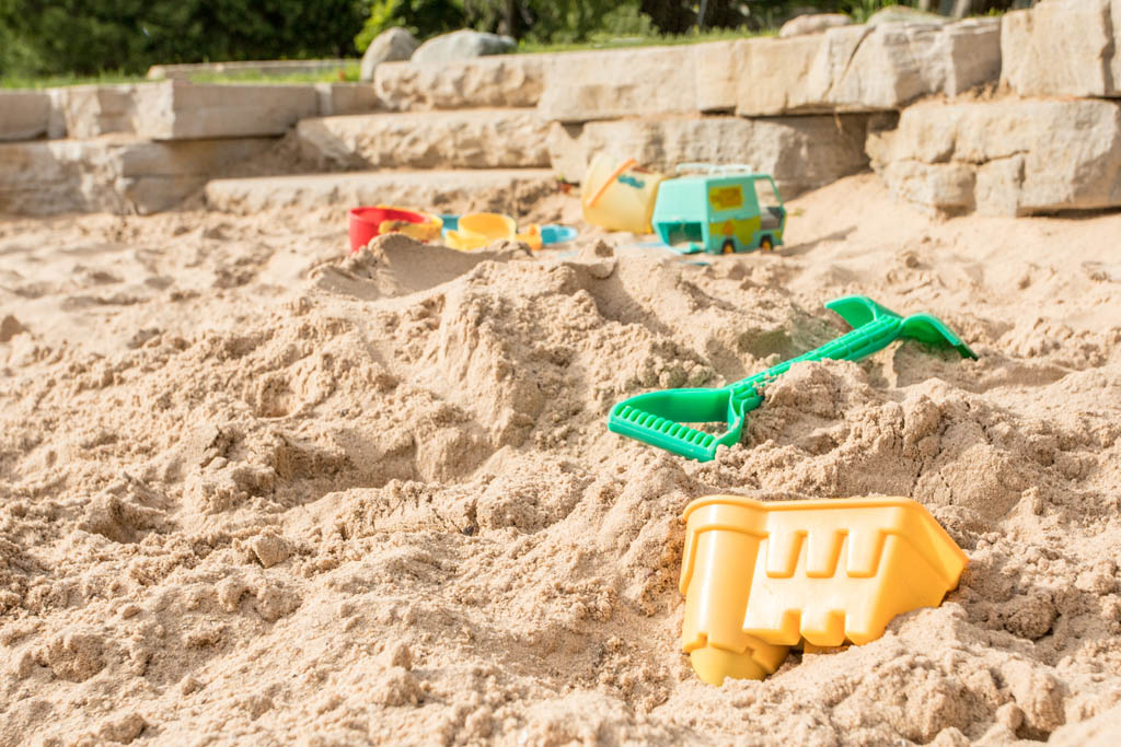 yellow plastic sand castle mold laying in sandbox