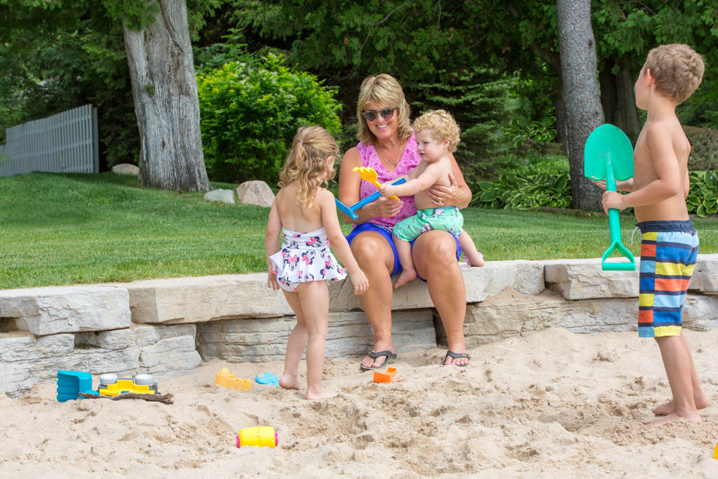 mom smiles while kids play in the sand