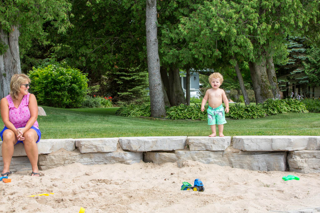 little boy walks around the sandbox walls