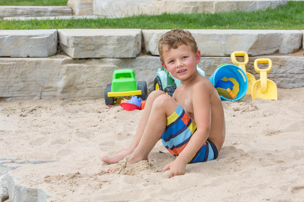 boy sitting in the sand with a green plastic toy tractor