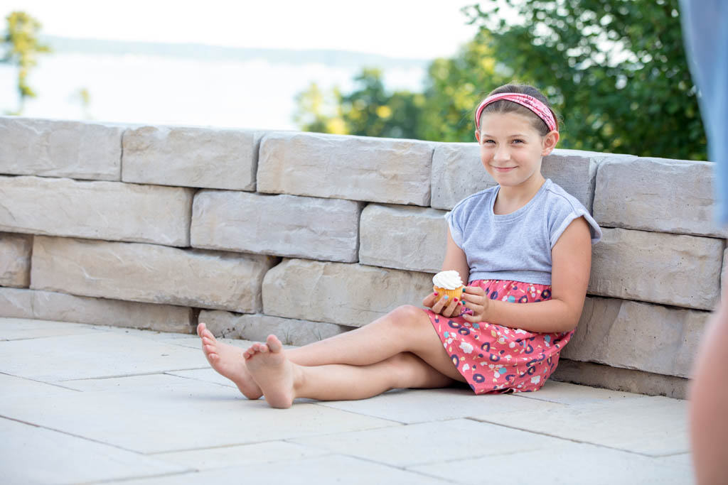 little girl sitting against the wall eating a cupcake