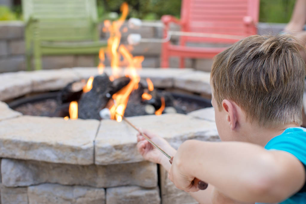 little boy roasting a marshmallow in the fire place