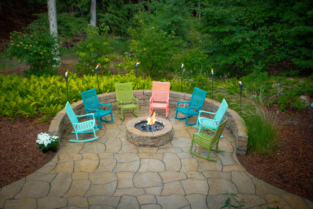 aerial view of multi colored rocking chairs on patio with fire place