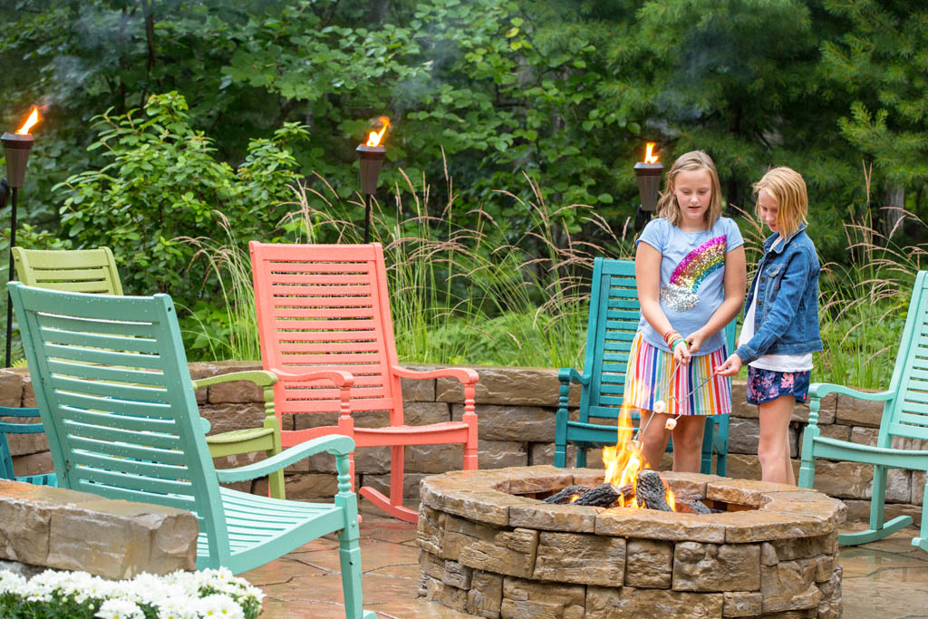 little girls stand over fire roasting marshmallows