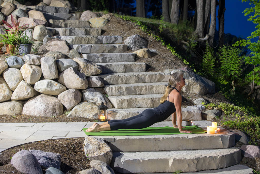 woman in yoga position in landscaped area