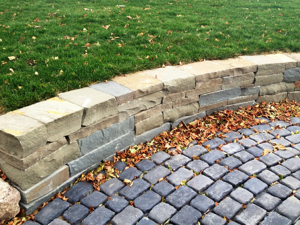 roughly hewn stone wall abutted agains round pavers