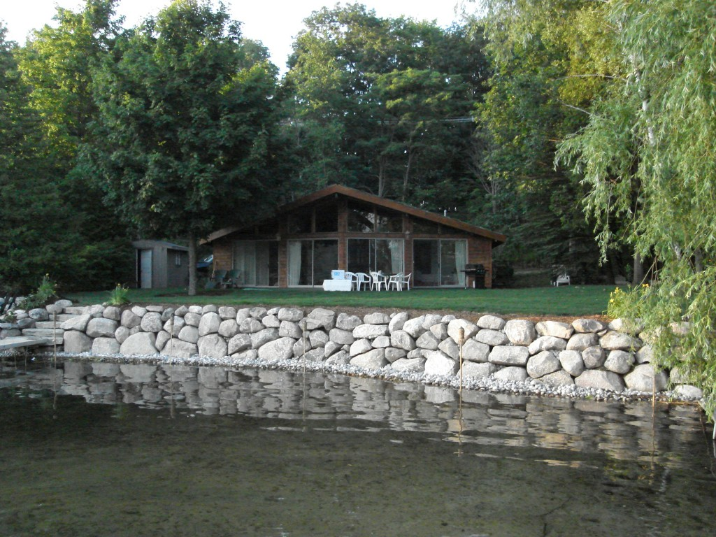 rock retaining wall between lake and lawn