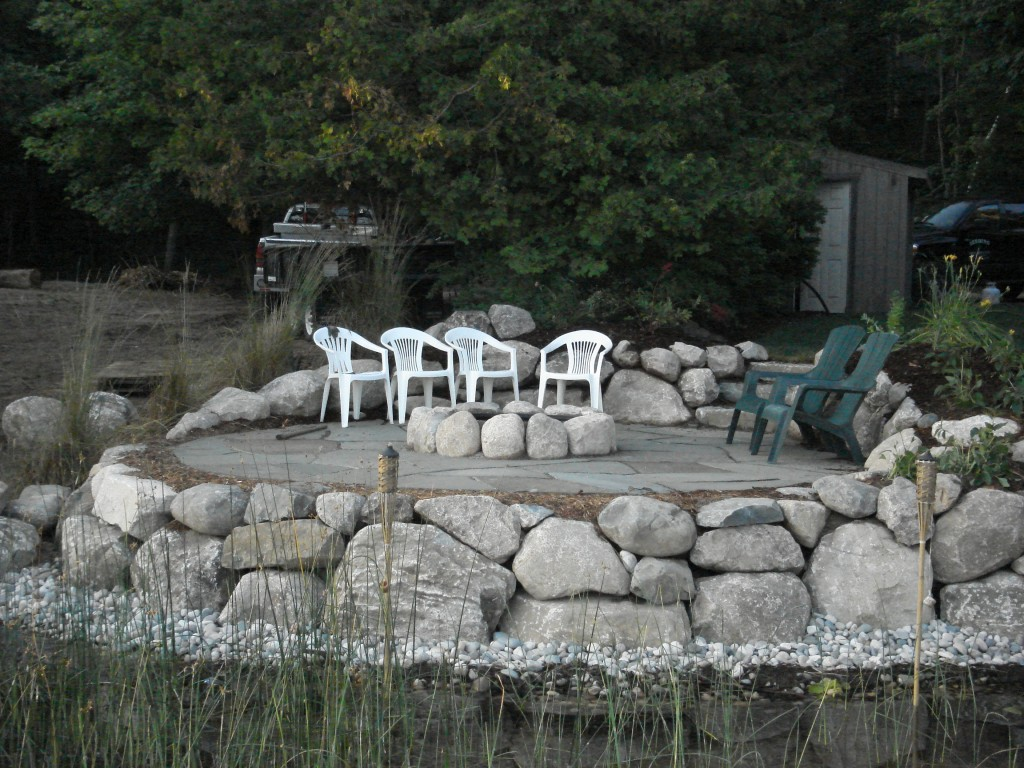 view of rocky fire pit and patio from lake