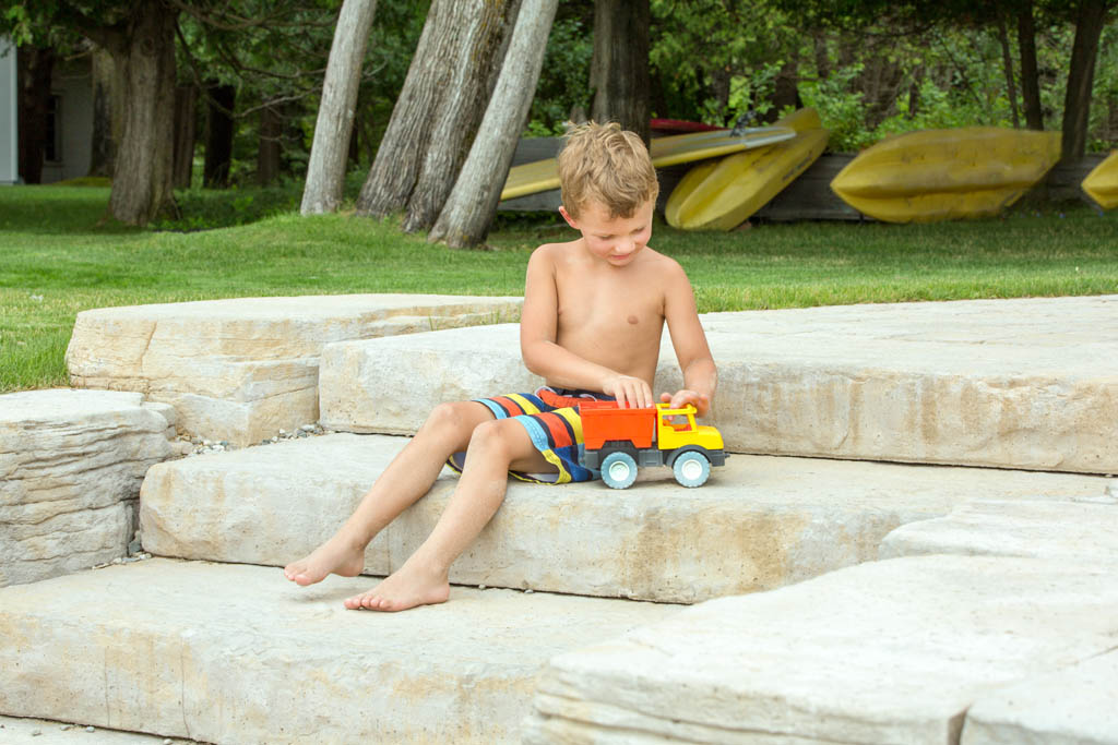 little boy sitting on stone stairs playing with toy truck